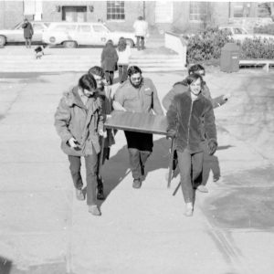 students carrying a table to Bernstein-Marcus Administration Center